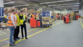 Drei Personen analysieren die Begebenheiten in einer Fabrikhalle.